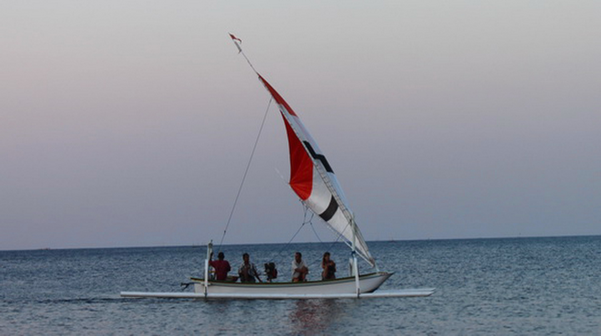 """Sunset sailing with outrigger boat """"Jukung"""" at Amed east Bali Indonesia"""